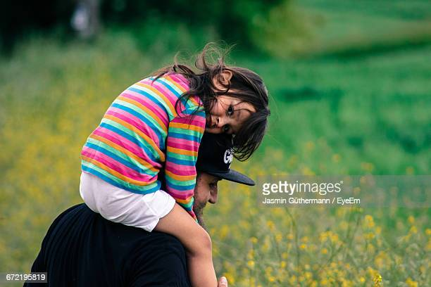 Portrait Of Girl Enjoying Ride On Shoulder From Father In Field