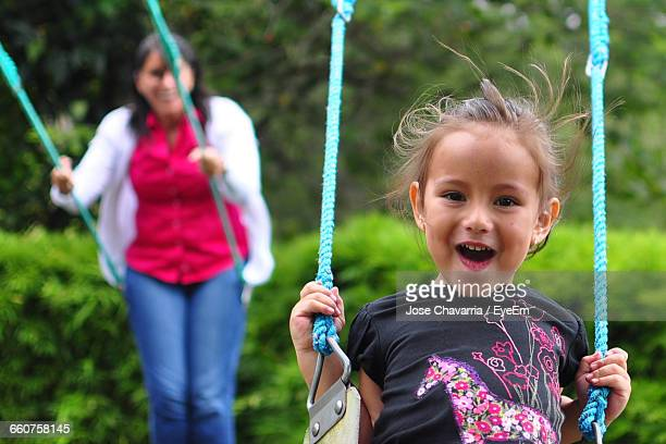 portrait of girl enjoying swing with mother at playground - ecuador fotografías e imágenes de stock