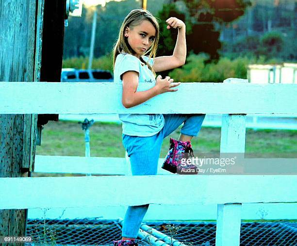 Portrait Of Girl Flexing Muscles While Standing By Railing