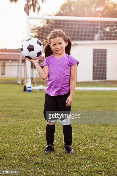 Portrait of girl football player holding up football on practice pitch