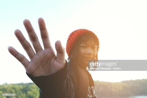 Portrait Of Girl Gesturing Stop Gesture Against Clear Sky