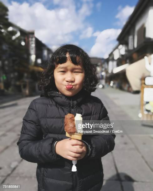 Portrait Of Girl Having Ice Cream On Street In Town Against Sky