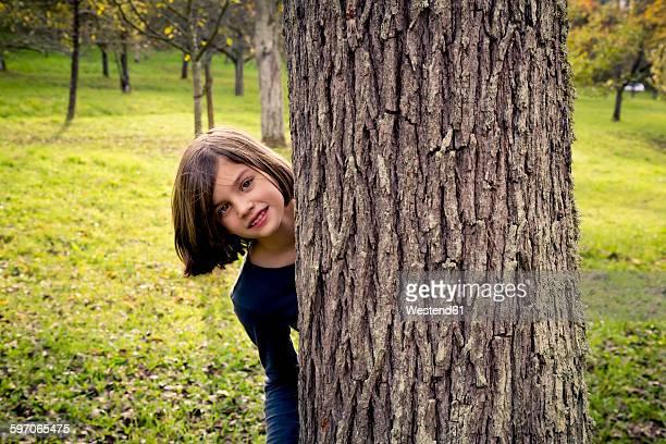 Portrait of girl hiding behind tree trunk