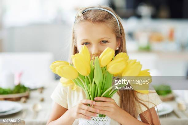 Portrait of girl holding and hiding behind yellow tulips