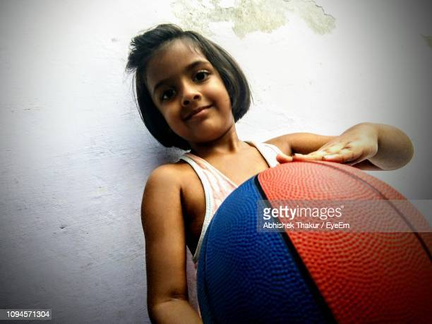 Portrait Of Girl Holding Ball Against Wall