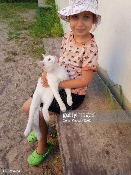 portrait of girl holding cat while sitting on seat - elena knouzi stock pictures, royalty-free photos & images