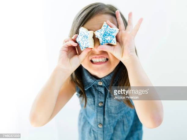 Portrait of girl (6-7) holding cookies in front of eyes
