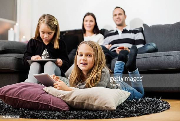 Portrait of girl holding digital tablet with family in living room