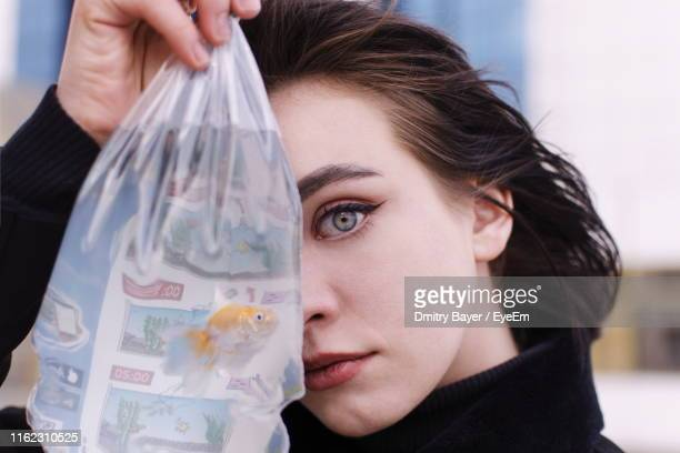 Portrait Of Girl Holding Fish In Plastic Bag Against Building And Sky
