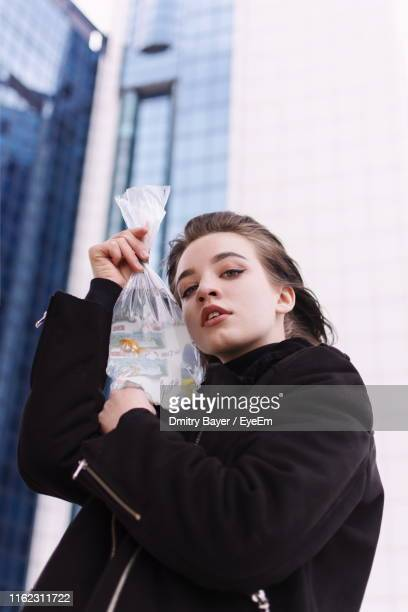 Portrait Of Girl Holding Fish In Plastic Bag While Standing Against Building