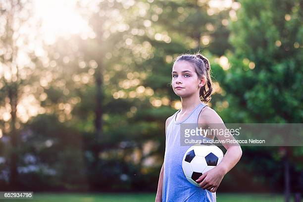 Portrait of girl holding football looking at camera