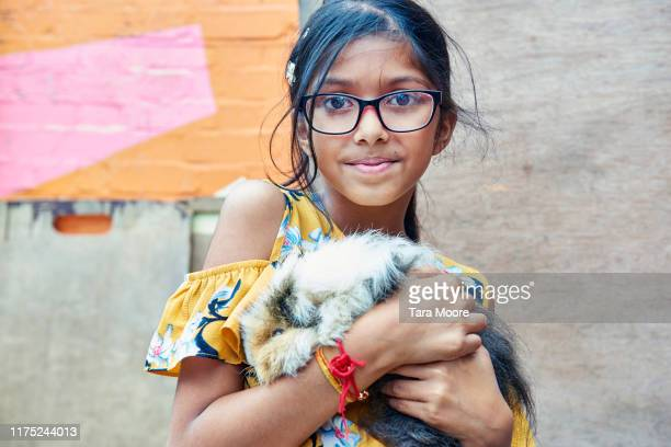 portrait of girl holding guinea pig - animal cruelty stock pictures, royalty-free photos & images