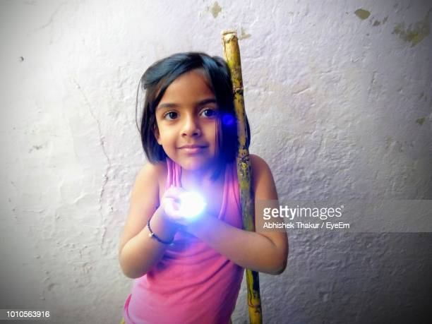 Portrait Of Girl Holding Illuminated Flash Light While Standing Against Wall