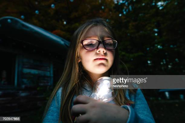 portrait of girl holding illuminated lightbulb in garden at dusk - heshphoto stock pictures, royalty-free photos & images
