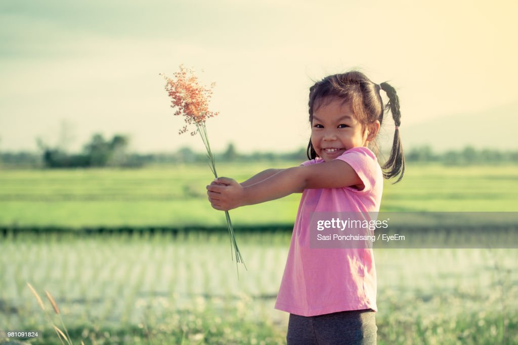 Portrait Of Girl Holding Plants While Standing On Field : Stock Photo