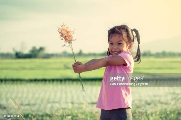 portrait of girl holding plants while standing on field - very young thai girls fotografías e imágenes de stock