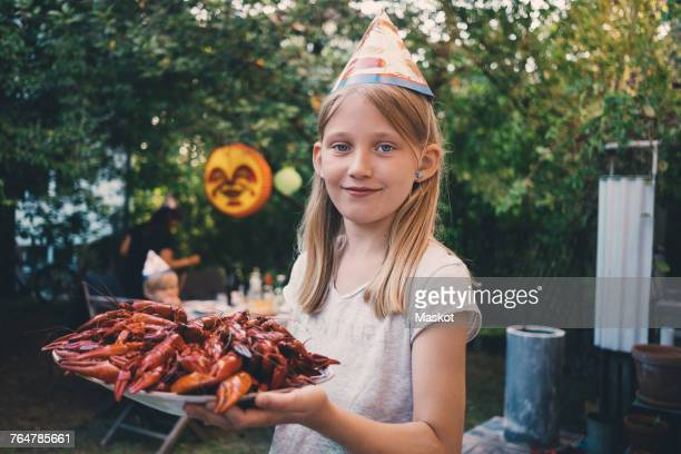 portrait of girl holding plate with cooked crayfish at garden dinner party - crayfish seafood stock pictures, royalty-free photos & images