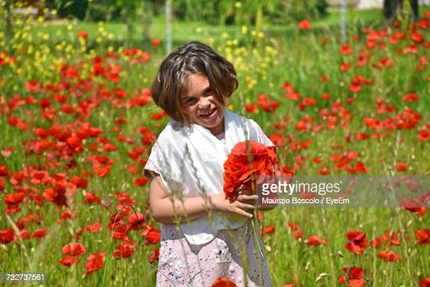 Portrait Of Girl Holding Poppy Flowers While Standing In Farm
