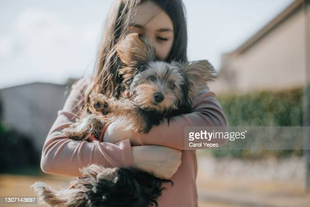 portrait of girl  ( 10 years)  holding puppy outdoors in windy day - 10 11 years stock pictures, royalty-free photos & images