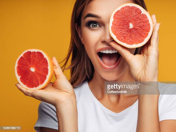 portrait of girl holding red grapefruit - grapefruit red stock pictures, royalty-free photos & images