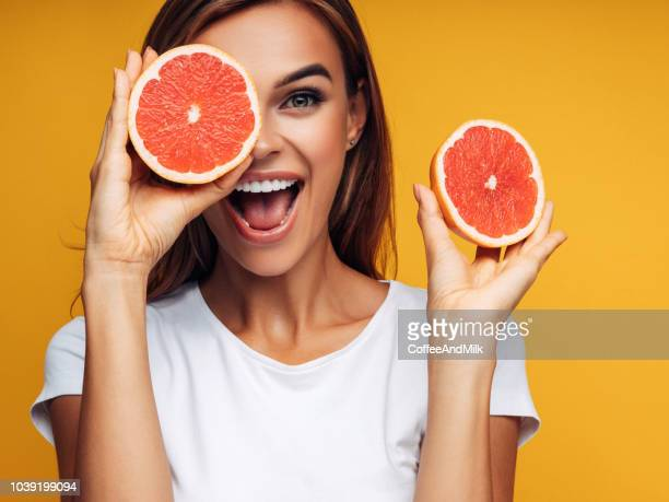 portrait of girl holding red grapefruit - citrus fruit stock pictures, royalty-free photos & images