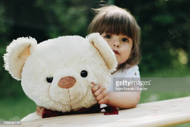 Portrait Of Girl Holding Teddy Bear While Standing By Wooden Railing