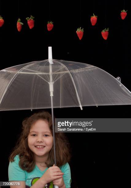 Portrait Of Girl Holding Umbrella With Strawberries Falling Against Black Background