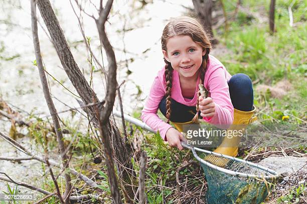 Portrait of girl holding up frog and fishing net