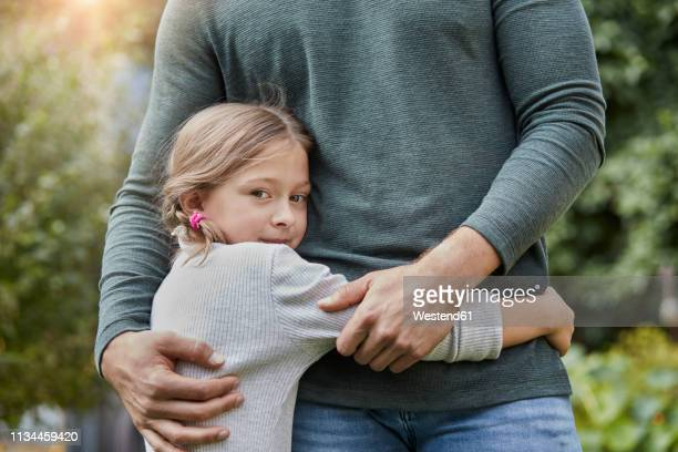 portrait of girl hugging father in garden - vertrauen stock-fotos und bilder