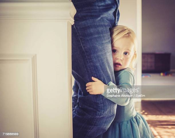 Portrait Of Girl Hugging Father Leg