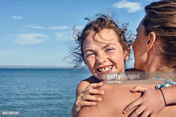 Portrait of girl hugging her mum on beach, smiling