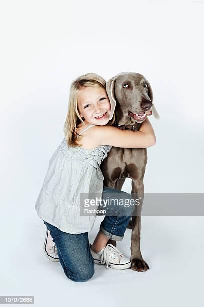Portrait of girl hugging her pet dog