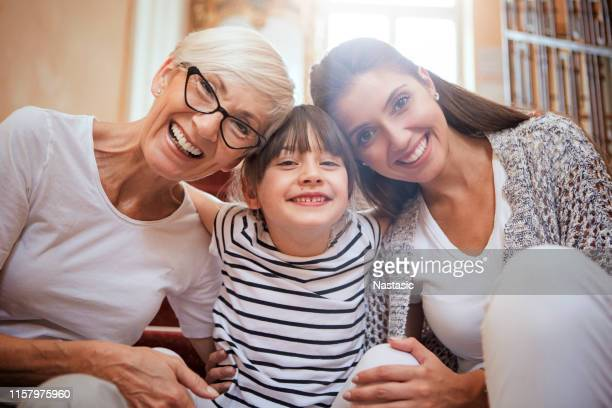 portrait of girl hugging mom and grandmother smiling - multi generation family stock pictures, royalty-free photos & images