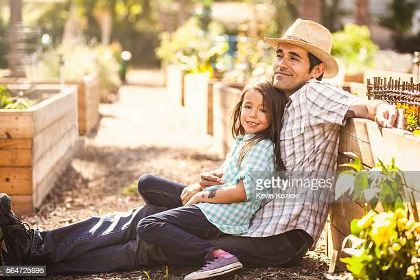 Portrait of girl in community garden sitting on fathers knee
