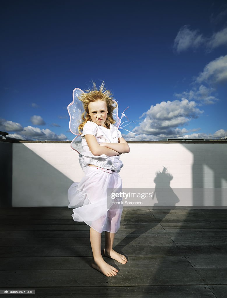 Portrait of girl (6-7) in fairy costume, standing on roof : Foto stock
