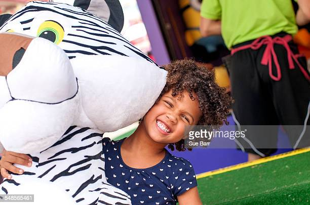 Portrait of girl in front of amusement stall carrying large prize tiger toy