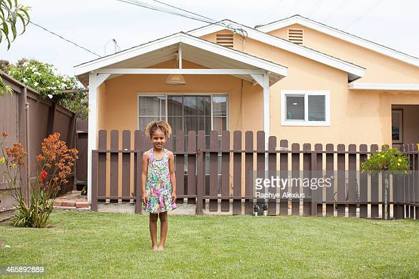 Portrait of girl in front of house