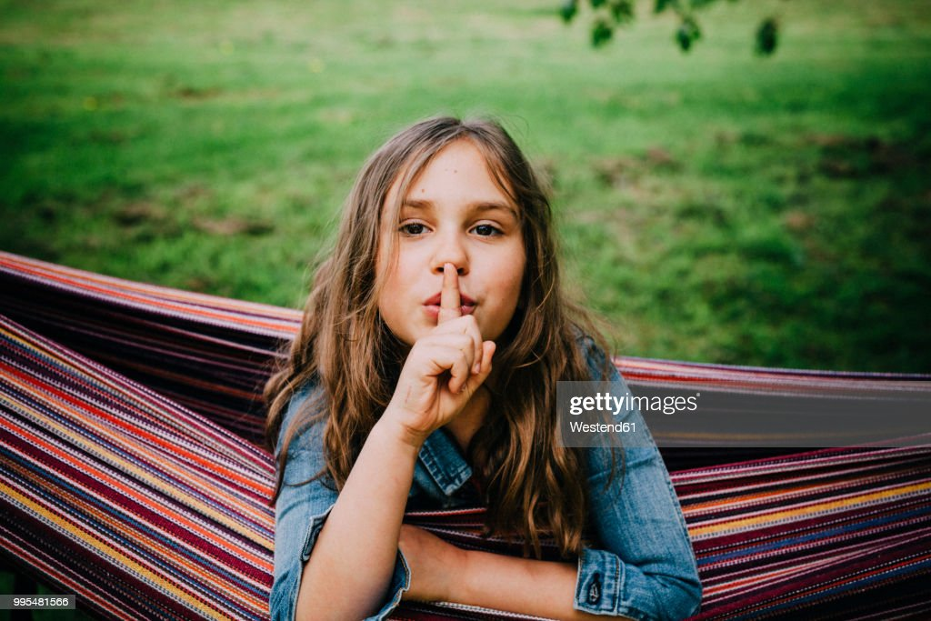 Portrait of girl in hammock with finger on her mouth : Stock-Foto