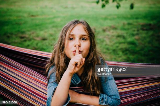 Portrait of girl in hammock with finger on her mouth