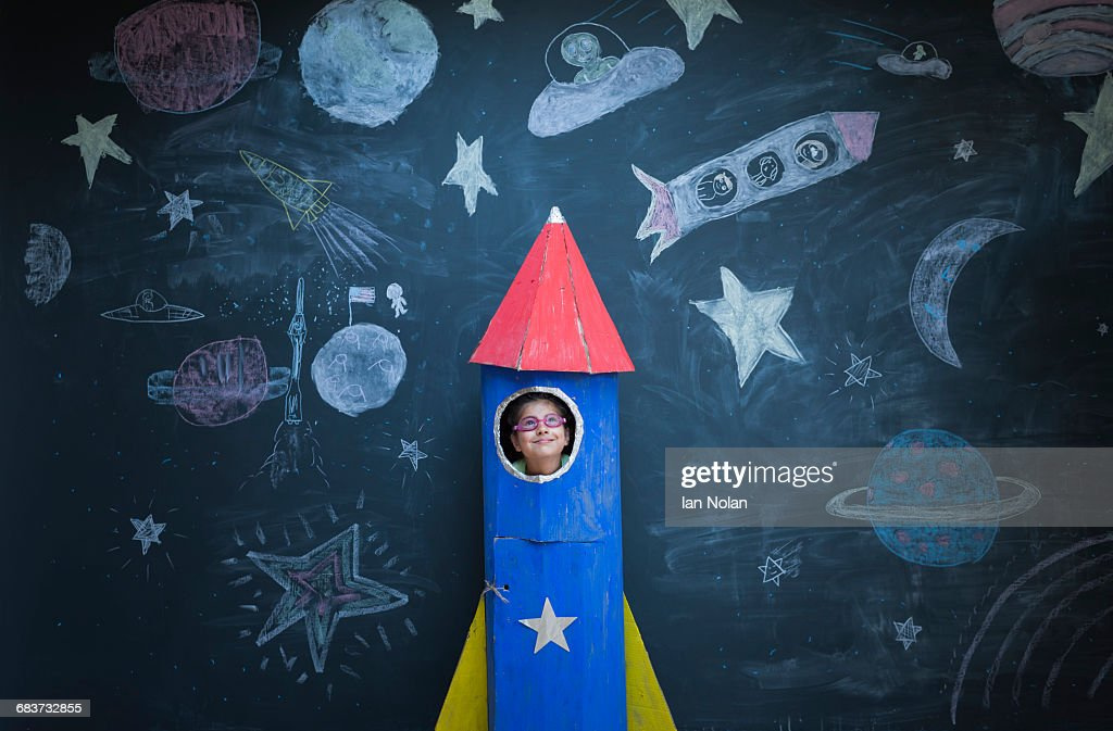 Portrait of girl in handmade space rocket in front of space themed chalk drawings : Stock Photo