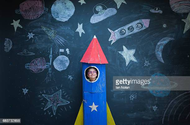 Portrait of girl in handmade space rocket in front of space themed chalk drawings