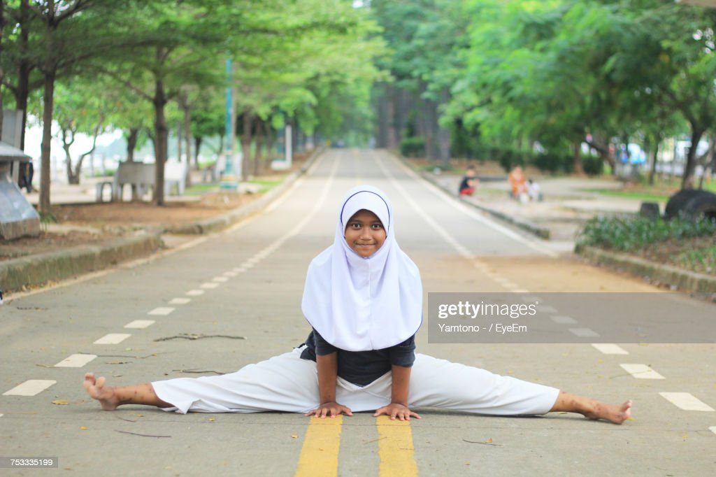 Portrait Of Girl In Hijab Doing Splits On Road : Foto de stock