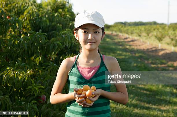 Portrait of girl (10-11) in orchard with handful of apricots