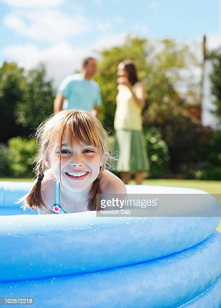 Portrait of girl in paddling pool, parents behind