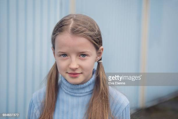 Portrait of girl (10-11) in pale blue sweater in front of pale blue garage doors