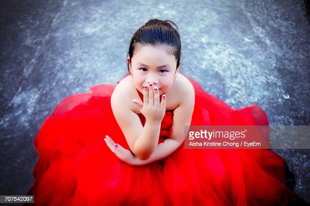 Portrait Of Girl In Red Dress Blowing Kiss While Sitting On Street