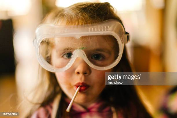 portrait of girl in safety goggles sucking lollipop - heshphoto stock pictures, royalty-free photos & images