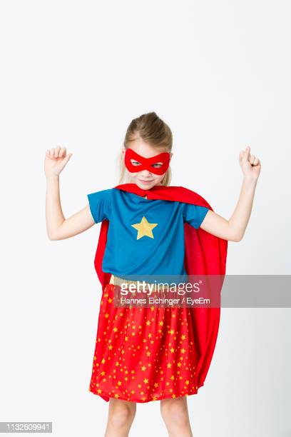portrait of girl in superhero costume standing against white background - mask disguise stock pictures, royalty-free photos & images