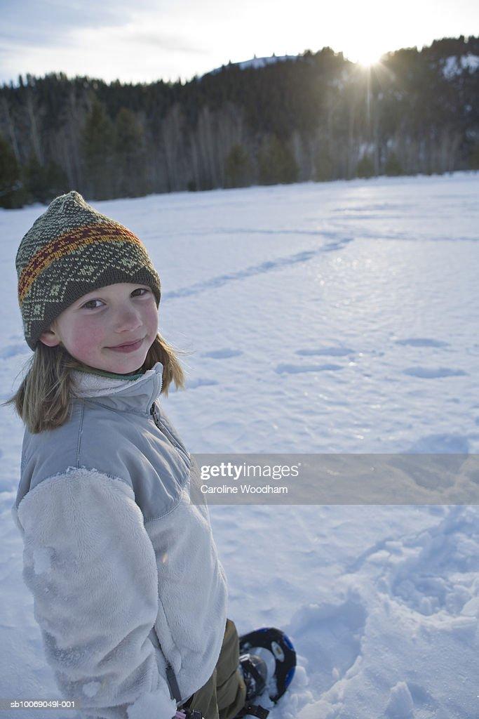 Portrait of girl (8-9) in winter landscape, solar flare : Stockfoto