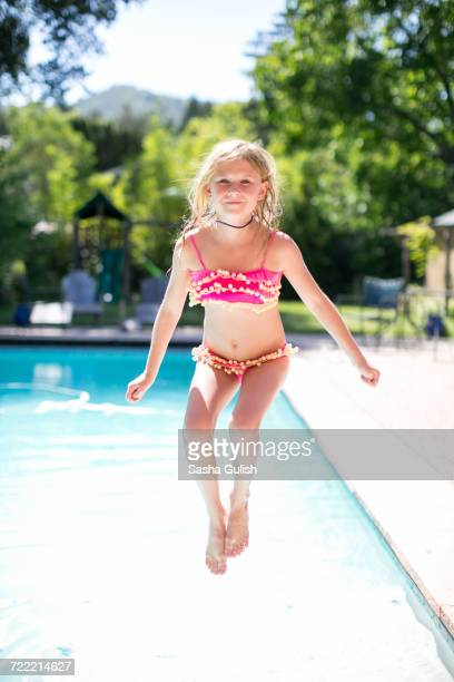 Portrait of girl jumping into outdoor swimming pool